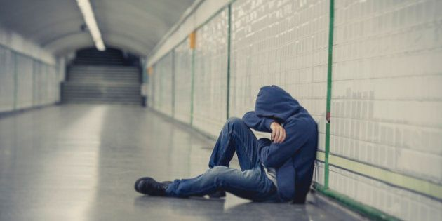 Young man abandoned lost in depression sitting on ground street subway tunnel suffering emotional pain,...