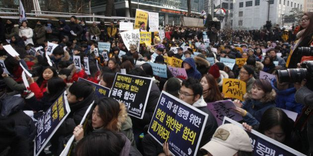SEOUL, Dec. 30, 2015-- People hold placards during a weekly anti-Japan protest in front of the Japanese...