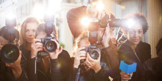 Portrait of paparazzi in a row with cameras and