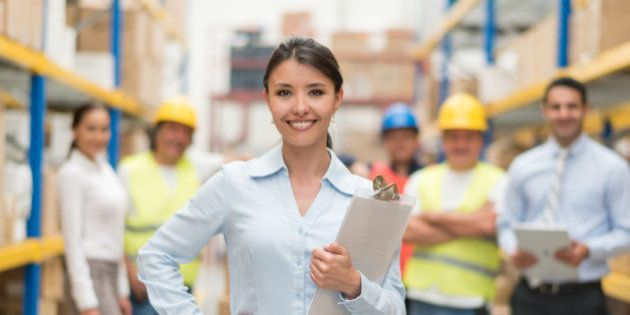 Business woman working at a warehouse with a group of people - freight transportation