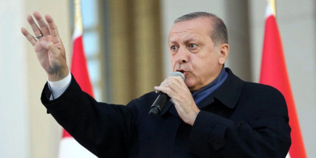 Turkish president Recep Tayyip Erdogan flashes a four finger sign called 'the rabia sign' as he delivers...