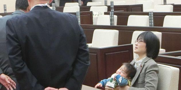2017年11月、熊本市議会に生後7カ月の長男を抱いたまま出席し、議会事務局職員らによる退席要請を拒否する緒方夕佳市議(右)=熊本市中央区
