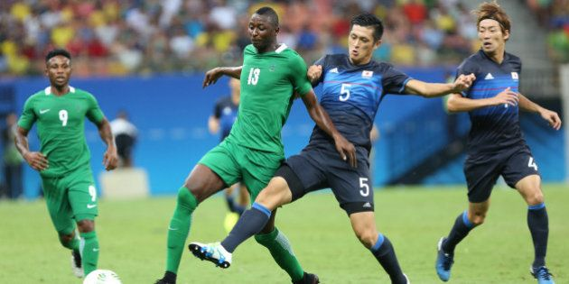 Nigeria's Sadiq Umar fights for the ball with Japan's Naomichi Ueda during a group B match of the men's...