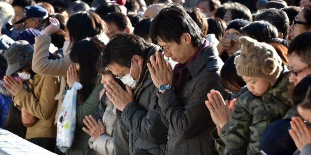 Japanese worshippers pray as they celebrate the New Year at Meiji shrine in Tokyo on January 1, 2015....