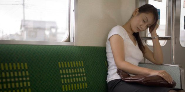 Young woman sitting on train holding bag on lap, eyes