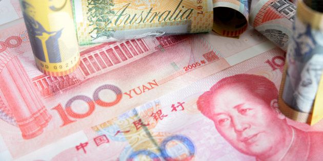 Australian dollar banknotes of various denominations and Chinese one-hundred yuan banknotes are arranged...