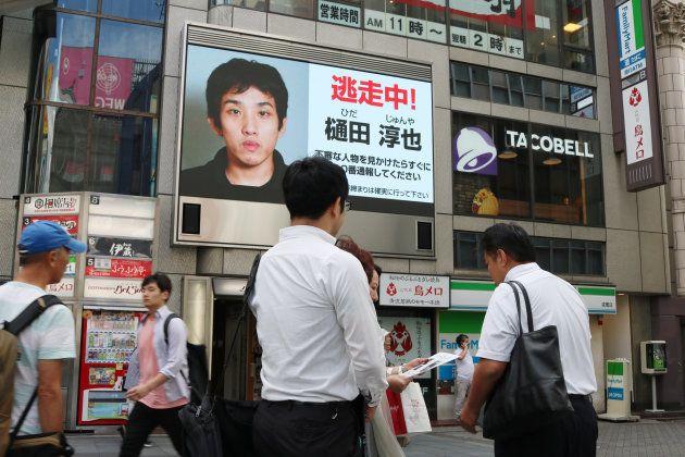 大阪・ミナミの繁華街のスクリーンに映し出された、富田林署から逃走した樋田淳也容疑者の画像と新たな手配書を配る大阪府警察の捜査員=9月11日、大阪市中央区