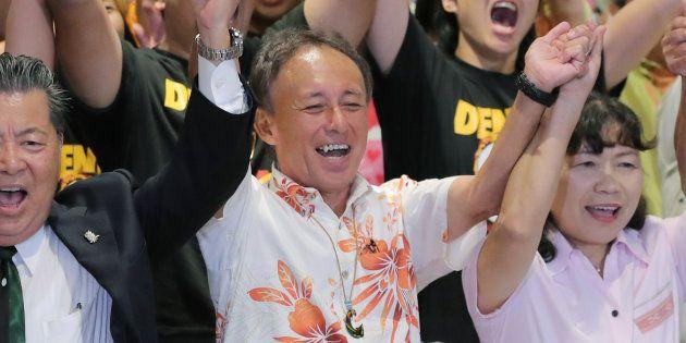 沖縄県知事選で勝利し、万歳する玉城デニー氏(中央)=9月30日夜、那覇市