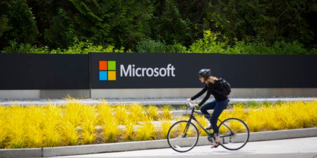 A woman rides a bicycle past a Microsoft Corp. sign on the company's main campus in Redmond, Washington,...