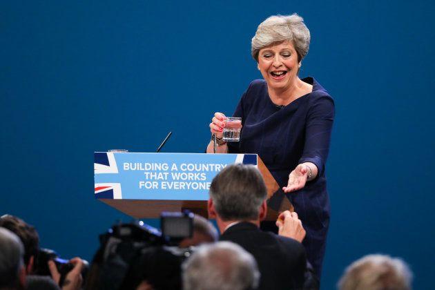 咳き込むメイ首相に、のど飴を渡すハモンド財務相。