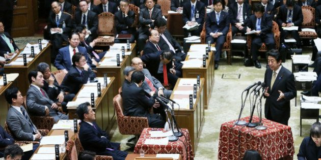 Shinzo Abe, Japan's prime minister, standing right, speaks during a budget committee session in the lower...