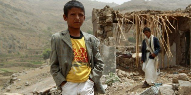 A Yemeni boy stands in front of a damaged house in the village of Bani Matar, 70 kilometers (43 miles)...