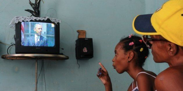 Cubans watch US President Barack Obama talking on TV about the reestablishment of full diplomatic ties...