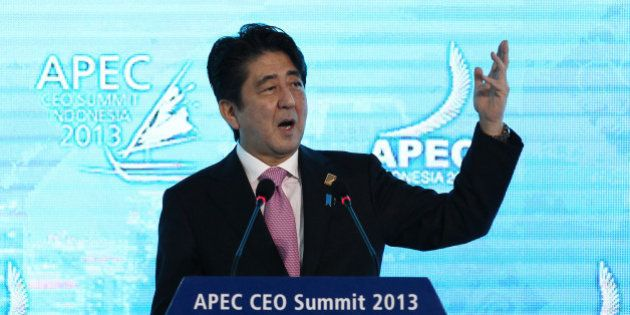 Shinzo Abe, Japan's prime minister, gestures as he delivers a keynote speech at the Asia-Pacific Economic...