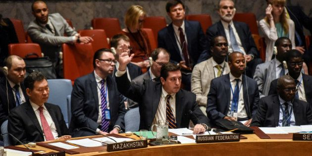 Russian Deputy Ambassador to the United Nations Vladimir Safronkov votes against a draft resolution condemning...