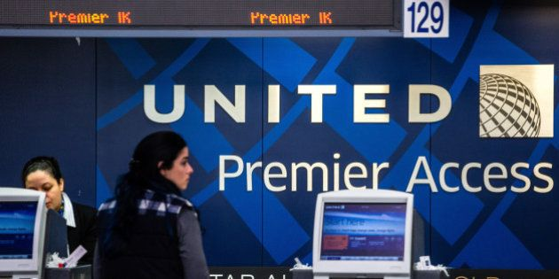 An employee assists a passenger inside the United Continental Holdings Inc. terminal at Newark Liberty...