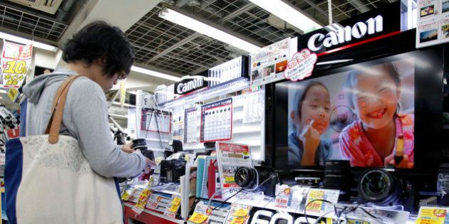 A customer looks at Canon Inc. digital cameras at an electronics store in Tokyo, Japan, on Thursday,...