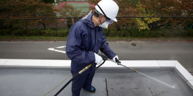 A worker sprays high pressure water during a decontamination process at a kindergarten in Hirono Town,...