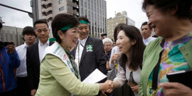 In this Friday, July 22, 2016 photo, former defense minister Yuriko Koike, left, shakes hands with a...