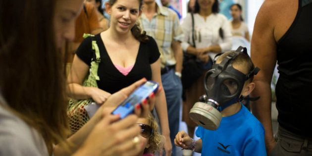 TEL AVIV, ISRAEL - AUGUST 26: (ISRAEL OUT) An Israeli tries on a gas mask as Israelis pick their gas...