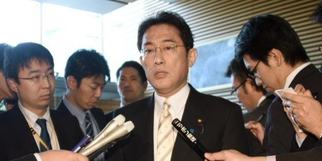 Surrounded by journalists, Japanese Foreign Minister Fumio Kishida (C) answers questions after a cabinet...