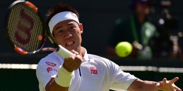 Japan's Kei Nishikori returns against Italy's Simone Bolelli during their men's singles first round match...