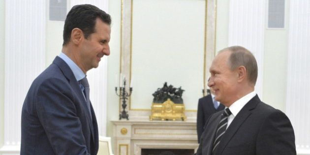 Russian President Vladimir Putin (R) shakes hands with Syrian President Bashar al-Assad during a meeting...