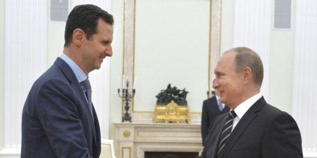 Russian President Vladimir Putin (R) shakes hands with Syrian President Bashar al-Assad during a meeting...