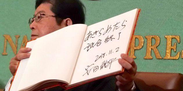 安田純平さんが記帳したサインを紹介する司会者。