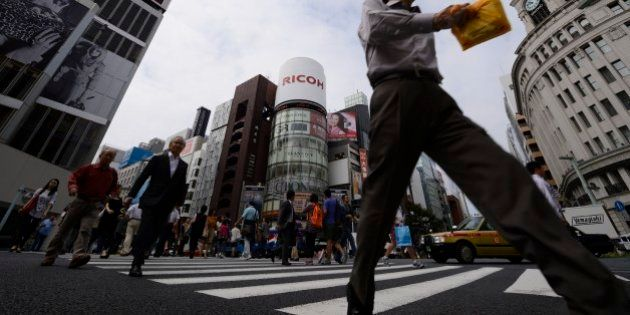 Pedestrians cross a street in the Ginza district of Tokyo, Japan, on Monday, Sept. 30, 2013. Large Japanese...