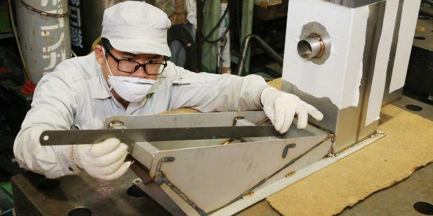金属加工工場で勤務するベトナム人技能実習生=9月3日、東京都大田区