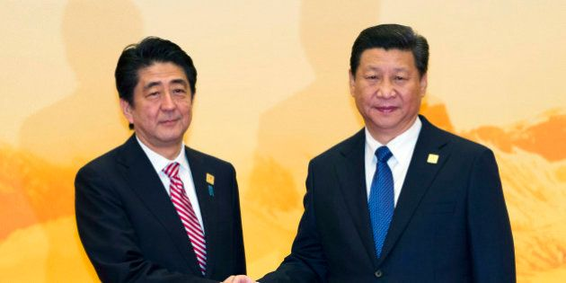 Japan's Prime Minister Shinzo Abe shakes hands with Chinese President Xi Jinping during a welcome ceremony...