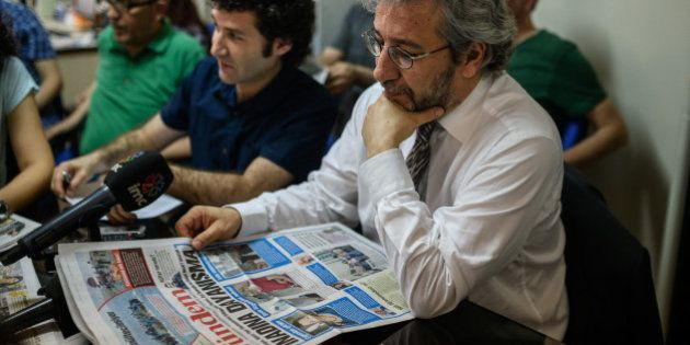 Cumhuriyet Daily newspaper Editor-in-chief Can Dundar (R), takes part in a news meeting at the Pro Kurdish...