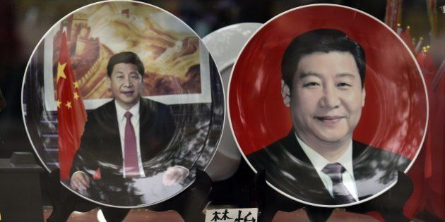 Decorative plates featuring Chinese President Xi Jinping are seen in a shop window in Beijing on October...