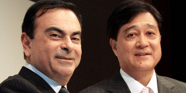 Carlos Ghosn, president and chief executive officer of Nissan Motor Co., left, shakes hands with Osamu...