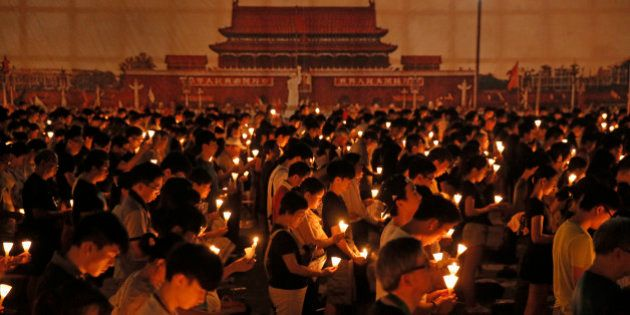 Tens of thousands of people attend a candlelight vigil at Victoria Park in Hong Kong Thursday, June 4,...