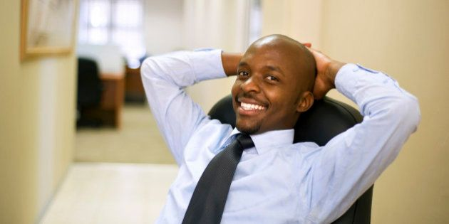 Businessman relaxes in a chair with hands behind his head in an office. Pretoria, South