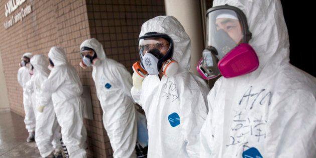 Workers dressed in protective suits and masks wait outside a building at J-Village, a soccer training...