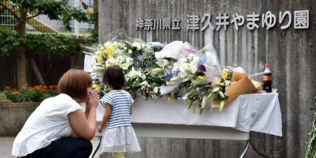 A mother and her daughter offer flowers for the victims of a knife rampage at the main entrance to the...