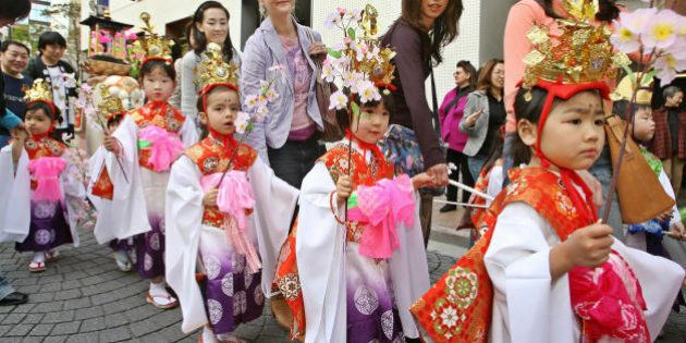 Tokyo, JAPAN: Girls wearing Japanese traditional costumes attend a parade on a street of Tokyo's Azabu-Juban,...