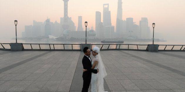 SHANGHAI, CHINA - NOVEMBER 07: (CHINA OUT) A newlywed couple takes wedding photos at the Bund as heavy...
