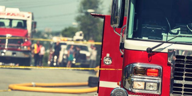 Firetrucks, caution tape, fire hoses and bystanders on the scene of a devastating house
