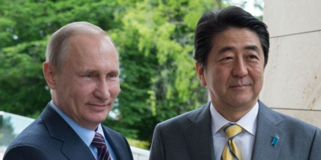 Russian President Vladimir Putin (L) welcomes Japanese Prime Minister Shinzo Abe during a meeting at...