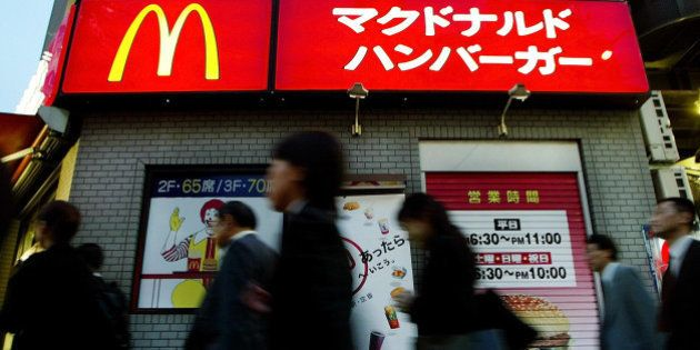 People haste their way home after work and go past a McDonald's hamburger shop in downtown Tokyo, Monday,...
