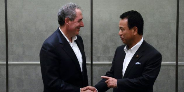 Michael Froman, U.S. trade representative, left, shakes hands with Akira Amari, Japan's minister of state...