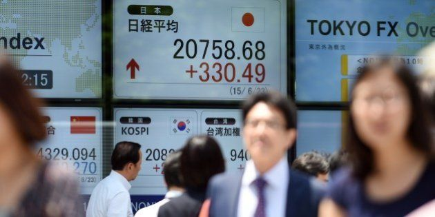 Businessmen walk in front of a securities company window flashing the current Tokyo stock prices in central...