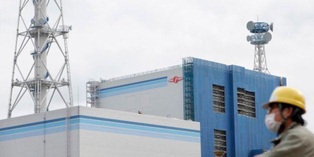 An employee cycles past Japan Atomic Power Co.'s Tokai Dai-Ni nuclear power station in Tokai Village,...