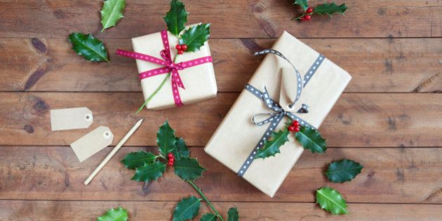 Decorating Christmas present with holly leaves on wooden