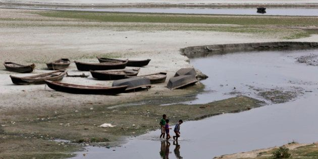 Indian children play near parked boats on the banks of river Ganges where water level has dried up in...