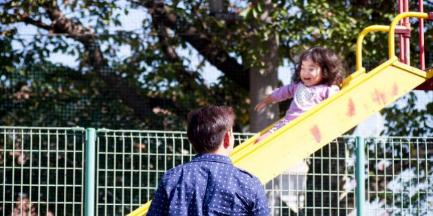 A little girl is sliding a slider at a park. She is happyly smiling. Her father is standing nearby and...